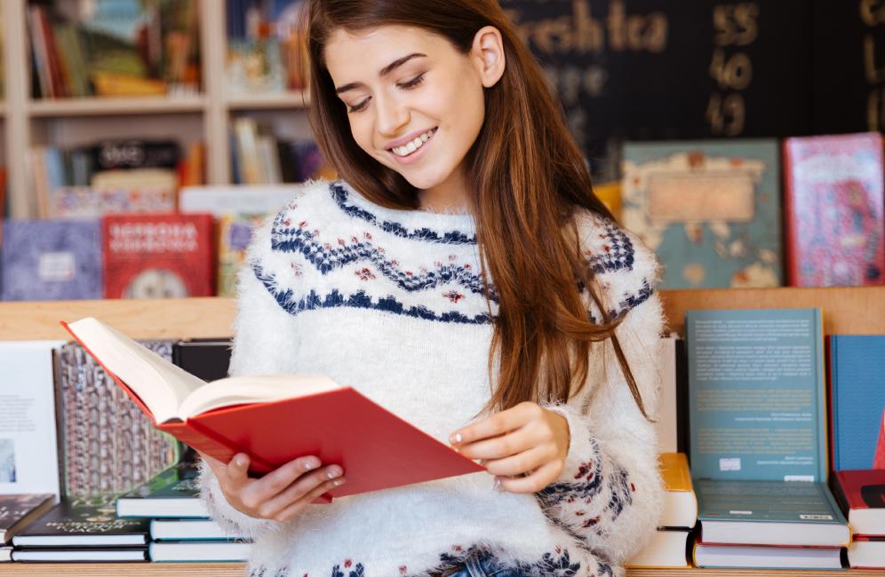 mujer sonríe lee un libro